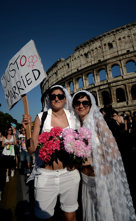 ". A couple dressed as brides holds a placard reading ""Just married\"" during the annual gay pride parade in downtown Rome on June 15, 2013. Tens of thousands of people paraded noisily on floats through the historic streets of Rome on June 15 to celebrate Gay Pride, amid calls for Italy to follow France\'s example in legalizing gay marriage.  AFP PHOTO/ FILIPPO  MONTEFORTE/AFP/Getty Images"