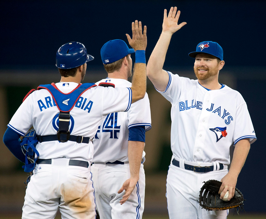 . Toronto Blue Jays Adam Lind, right, celebrates with teammates J.P. Arencibia, left, and Casey Janssen, middle, after defeating the Colorado Rockies in a baseball game in Toronto on Wednesday, June 19, 2013. (AP Photo/The Canadian Press, Frank Gunn)