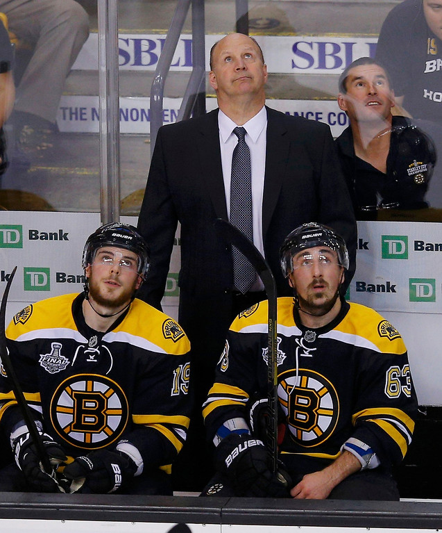 . Boston Bruins head coach Claude Julien watches a replay with players Tyler Seguin (L) and Brad Marchand during the first period against the Chicago Blackhawks in Game 4 of their NHL Stanley Cup Finals hockey series in Boston, Massachusetts, June 19, 2013. REUTERS/Brian Snyder