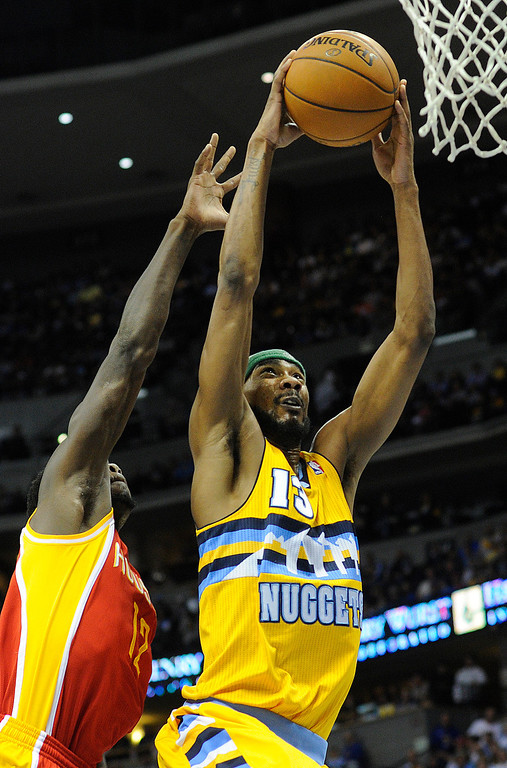 . DENVER, CO. - APRIL 6: Corey Brewer (13) of the Denver Nuggets breezed past Patrick Beverley (12) of the Houston Rockets in the second half. The Denver Nuggets defeated the Houston Rockets 132-114 at the Pepsi Center Saturday night, April 6, 2013. Photo By Karl Gehring/The Denver Post)