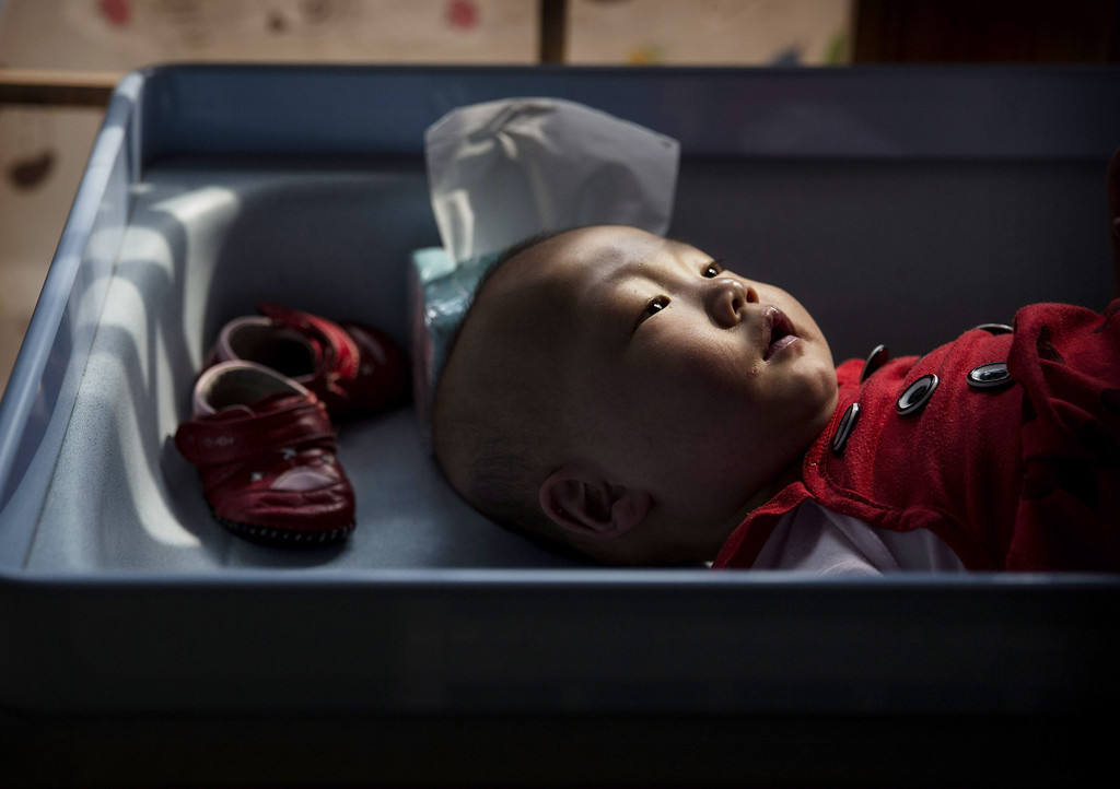 . A young orphaned Chinese girl lays on a changing table at a foster care center on April 2, 2014 in Beijing, China.  (Photo by Kevin Frayer/Getty Images)