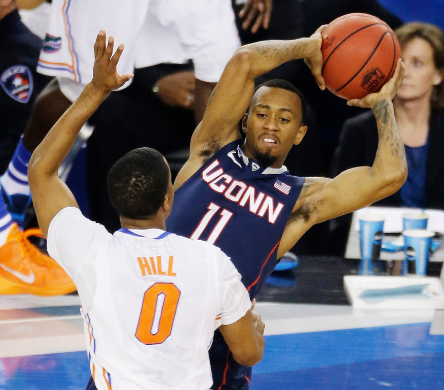 . Connecticut guard Ryan Boatright (11) looks to pass around Florida guard Kasey Hill (0) during the first half of the NCAA Final Four tournament college basketball semifinal game Saturday, April 5, 2014, in Arlington, Texas. (AP Photo/Tony Gutierrez)