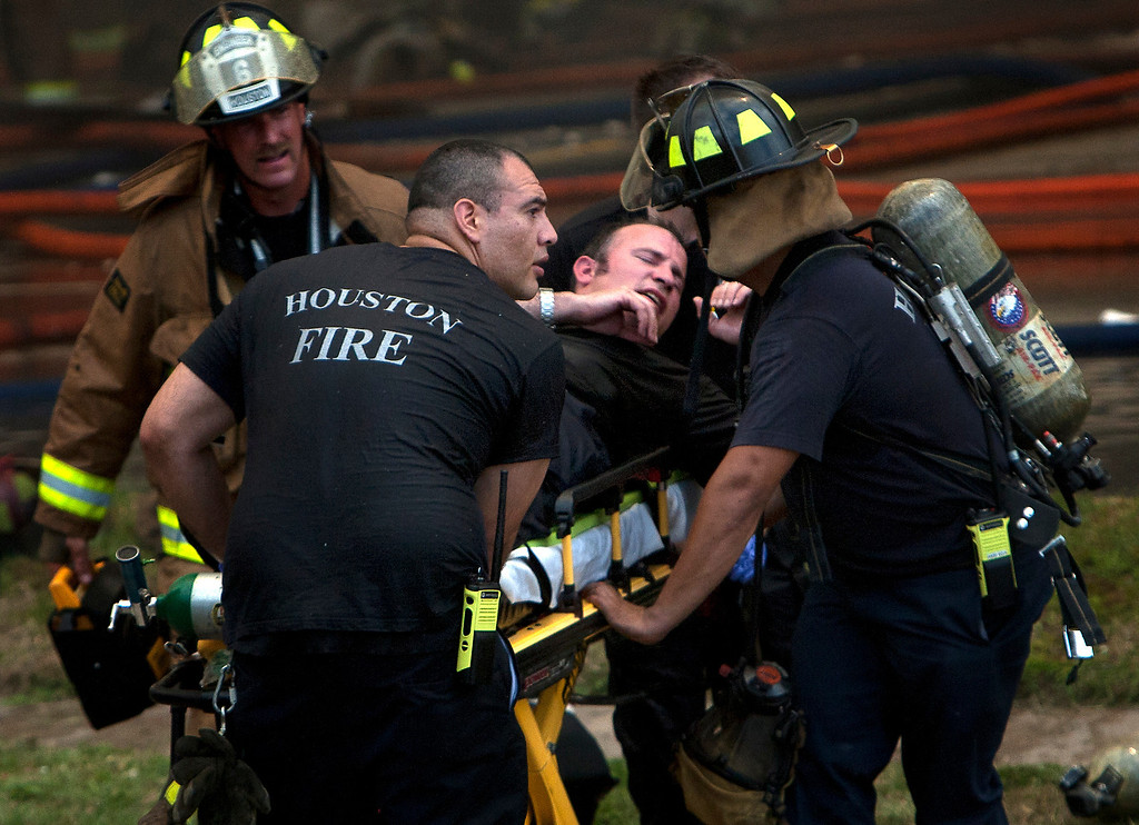 . A firefighter is wheeled to an ambulance after fighting a fire at the Southwest Inn, Friday, May 31, 2013, in Houston. Four firefighters have died and at least five people have been hospitalized. (AP Photo/Houston Chronicle, Cody Duty)