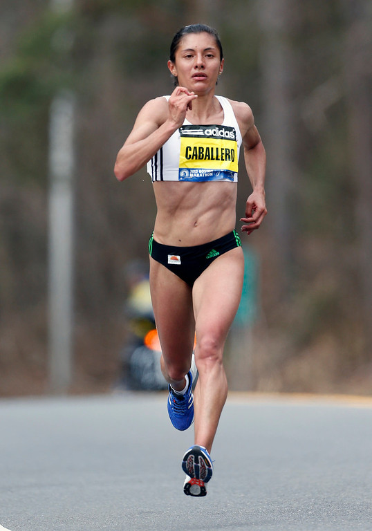 . Yolanda Caballero runs alone at the twelve-mile mark on the Boston Marathon course in Wellesley, Mass., Monday, April 15, 2013. (AP Photo/Michael Dwyer)