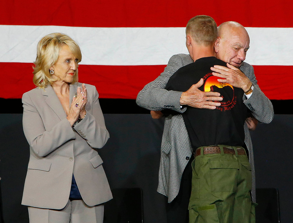 . Arizona Gov. Jan Brewer, left, looks on as Brendan McDonough, the only surviving member of his crew, right, receives a hug from Prescott, Ariz. Mayor Marlin Kuykendall, during a memorial service at Tim\'s Toyota Center in Prescott Valley, Ariz.,  Tuesday, July 9, 2013, for the 19 Granite Mountain hotshot firefighters that were killed on June 30 while battling the Yarnell Hill Fire. (AP Photo/The Arizona Republic, David Kadlubowski, Pool)