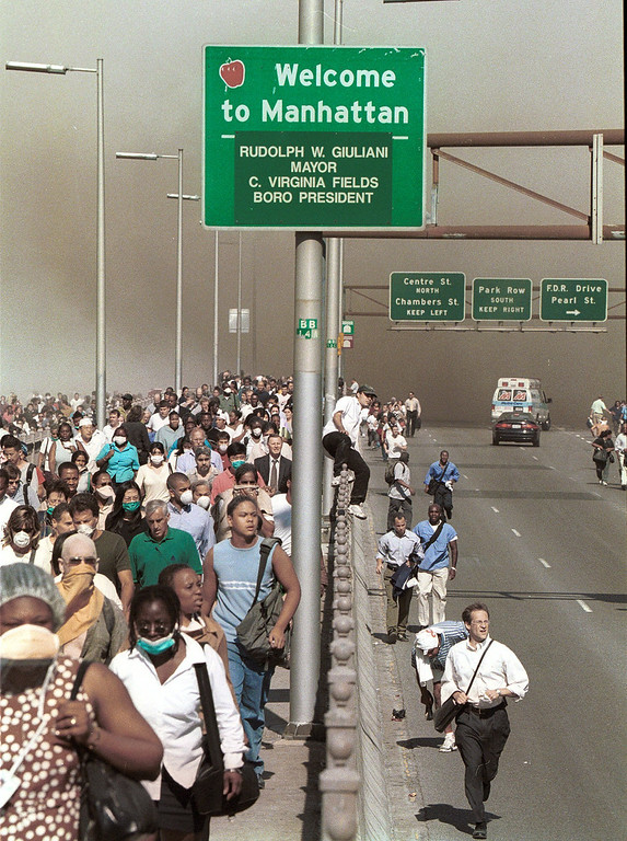 . People flee lower Manhattan across the Brooklyn Bridge in New York, Tuesday, Sept. 11, 2001, following a terrorist attack on the World Trade Center. (AP Photo/Daniel Shanken)