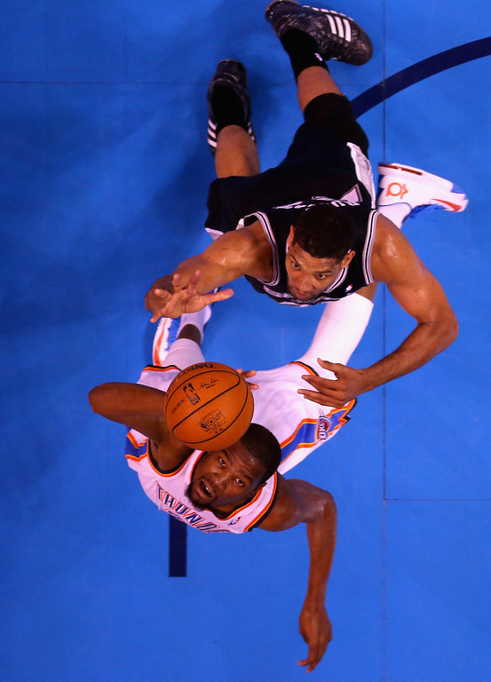 . OKLAHOMA CITY, OK - MAY 27:  Tim Duncan #21 of the San Antonio Spurs and Kevin Durant #35 of the Oklahoma City Thunder go up for a loose ball in the first half during Game Four of the Western Conference Finals of the 2014 NBA Playoffs at Chesapeake Energy Arena on May 27, 2014 in Oklahoma City, Oklahoma. (Photo by Ronald Martinez/Getty Images)
