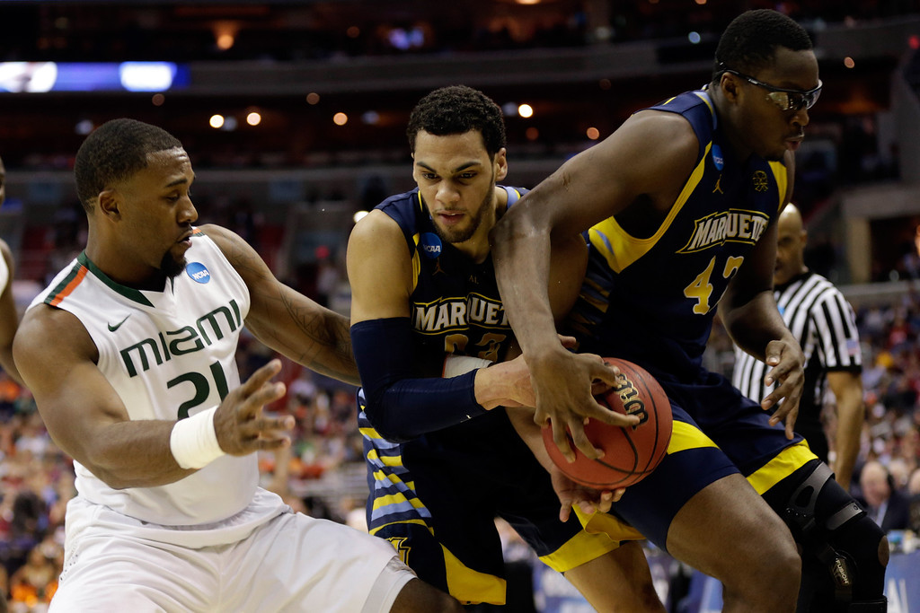 . WASHINGTON, DC - MARCH 28:  Erik Swoope #21 of the Miami (Fl) Hurricanes fights for the loose ball against Jake Thomas #23 and Chris Otule #42 of the Marquette Golden Eagles during the East Regional Round of the 2013 NCAA Men\'s Basketball Tournament at Verizon Center on March 28, 2013 in Washington, DC.  (Photo by Win McNamee/Getty Images)