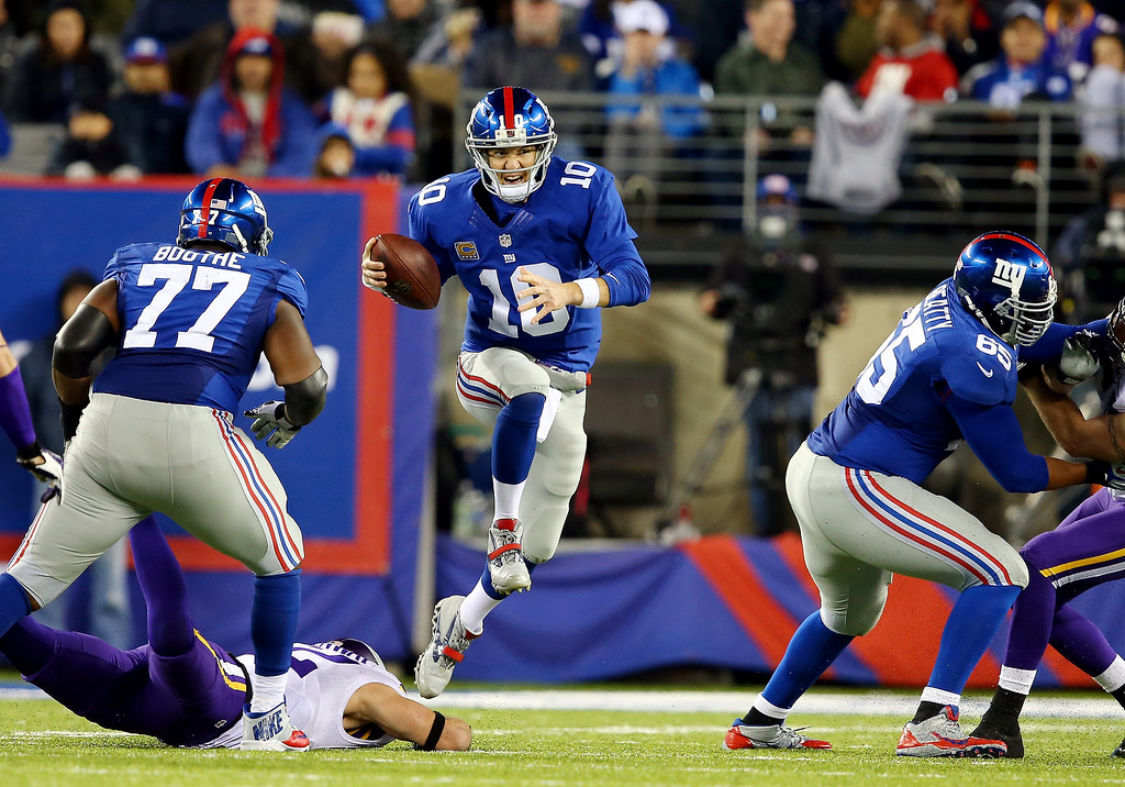 . Quarterback Eli Manning #10 of the New York Giants avoids a tackle against the Minnesota Vikings during a game at MetLife Stadium on October 21, 2013 in East Rutherford, New Jersey.  (Photo by Elsa/Getty Images)