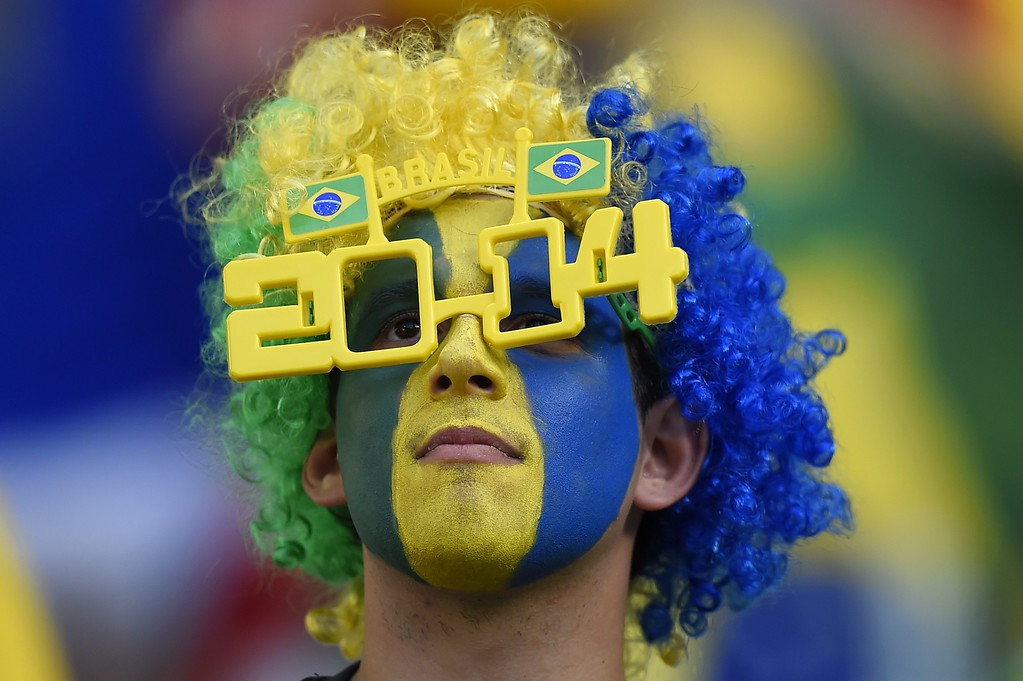 . TOPSHOTS  A Brazil\'s supporter cheers prior to the quarter-final football match between Brazil and Colombia at the Castelao Stadium in Fortaleza during the 2014 FIFA World Cup on July 4, 2014.    AFP PHOTO / FABRICE COFFRINIFABRICE COFFRINI/AFP/Getty Images