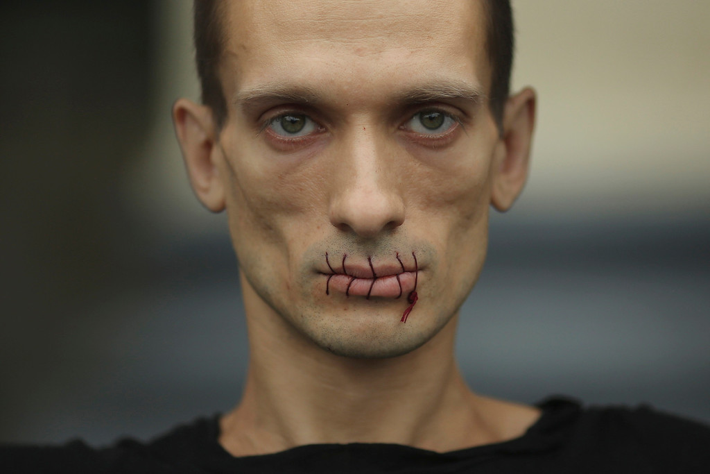 """. Artist Pyotr Pavlensky, a supporter of jailed members of female punk band \""""Pussy Riot\"""", looks on with his mouth sewed up as he protests outside the Kazan Cathedral in St. Petersburg, July 23, 2012. A court on Monday rejected a request to call President Vladimir Putin and the head of the Russian Orthodox Church to testify in the trial of three female punk rockers who derided Putin in a protest in the country\'s main cathedral, their lawyer said. REUTERS/Trend Photo Agency/Handout"""