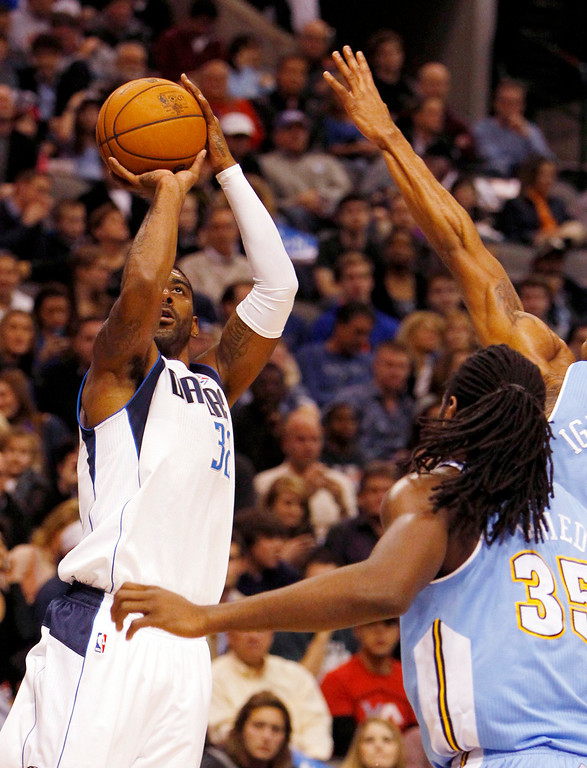 . The Dallas Mavericks\' O.J. Mayo (32) puts up a shot against the Denver Nuggets\' Kenneth Faried (35) and Andre Iguodala at the American Airlines Center in Dallas, Texas, on Friday, December 28, 2012. (Richard W. Rodriguez/Fort Worth Star-Telegram/MCT)