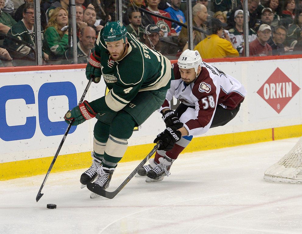 . Minnesota Wild defenseman Clayton Stoner (4) skates the puck behind the Colorado Avalanche goal as he gets chased by Colorado Avalanche left wing Patrick Bordeleau (58) during the second period April 24, 2014 in Game 4 of the Stanley Cup Playoffs at Xcel Energy Center. (Photo by John Leyba/The Denver Post)
