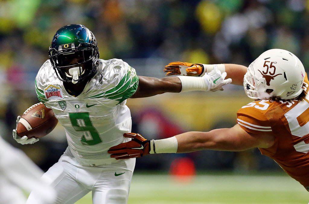 . Running back Byron Marshall #9 of the Oregon Duckss carries the ball as linebacker Dalton Santos #55 of the Texas Longhorns tries to make the tackle during the Valero Alamo Bowl at the Alamodome on December 30, 2013 in San Antonio, Texas.  (Photo by Ronald Martinez/Getty Images)