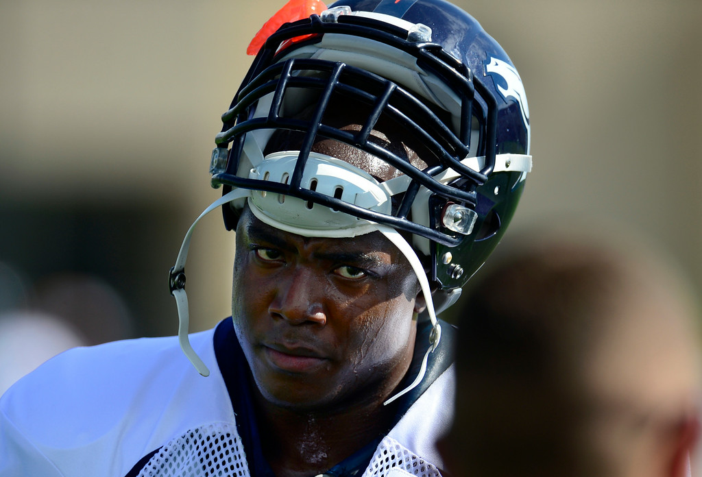 . DeMarcus Ware (94) takes a quick rest between drills on Saturday. The Denver Broncos football team hold their workouts for the team during mini-camp at Dove Valley in Centennial on Saturday, July 26, 2014. (Photo by Kathryn Scott Osler/The Denver Post)