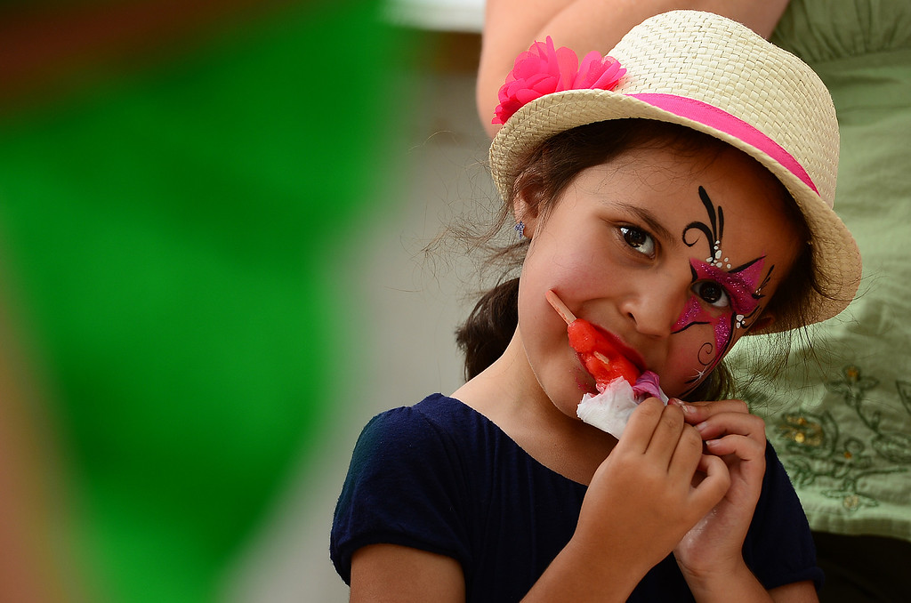 . Arianna Quarrell, 5, enjoys a cool popsicle at  the Taste of Colorado at Civic Center Park in Denver on Sunday, August 31, 2014.  The festival, which offers many different types of food such as gigantic turkey legs, corn on the cob and ice cream, wraps up on Monday, September 1.  (Photo By Helen H. Richardson/ The Denver Post)