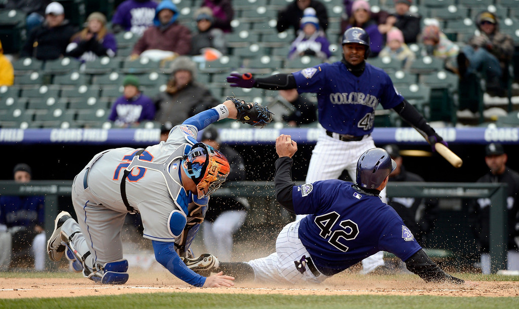 . John Buck of the New York Mets tries to tag out a sliding Michael Cuddyer of the Colorado Rockies at home during the second inning April 16, 2013 at Coors Field. Cuddyer was safe on the play on a Wilin Rosario single. (Photo By John Leyba/The Denver Post)