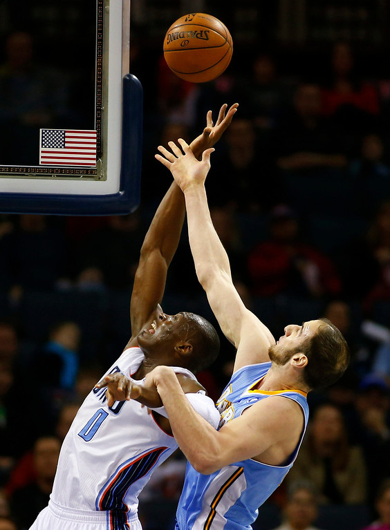 . Charlotte Bobcats power forward Bismack Biyombo of Democratic Republic of Congo (L) fights for a rebound against Denver Nuggets center Kosta Koufos during the first half of their NBA basketball game in Charlotte, North Carolina February 23, 2013. REUTERS/Chris Keane