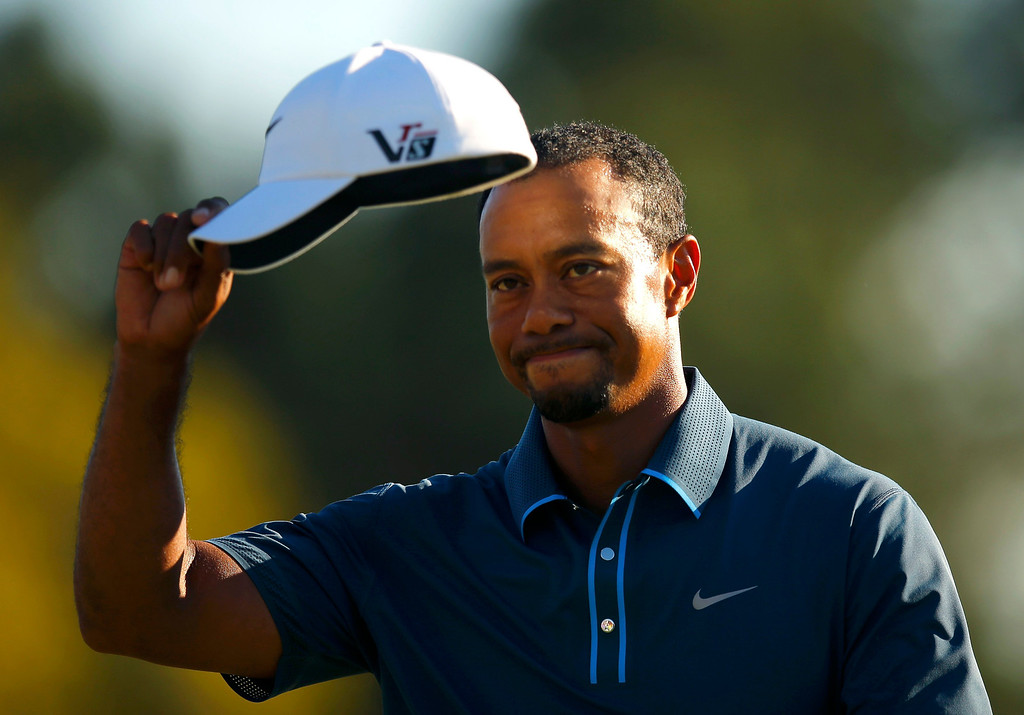 . Tiger Woods of the U.S. tips his hat after sinking a par putt on the 18th green during third round play in the 2013 Masters golf tournament at the Augusta National Golf Club in Augusta, Georgia, April 13, 2013.   REUTERS/Brian Snyder