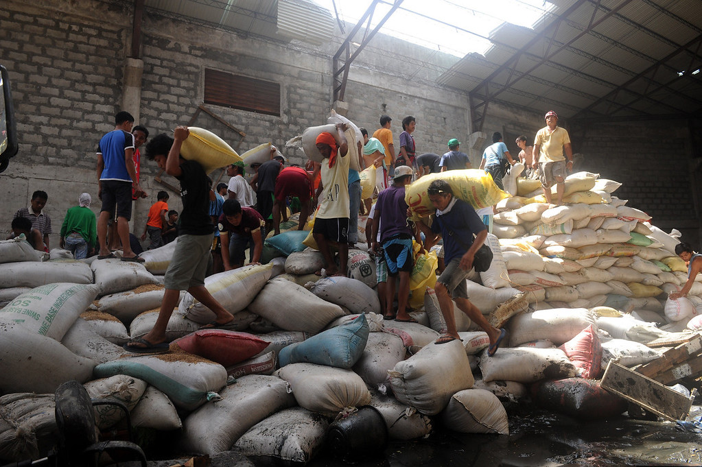 . Residents loot water damaged sacks of rice from a rice warehouse in the aftermath of Super Typhoon Haiyan in Tacloban in the eastern Philippine island of Leyte on November 11, 2013. The United States, Australia and the United Nations mobilized emergency aid to the Philippines as the scale of the devastation unleashed by Super Typhoon Haiyan emerged on November 11.  NOEL CELIS/AFP/Getty Images