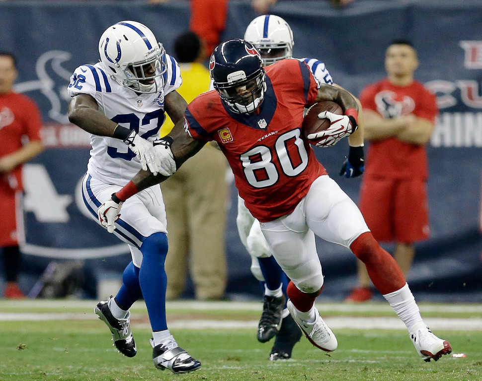 . Houston Texans\' Andre Johnson (80) fends off Indianapolis Colts\' Cassius Vaughn, left, after making a catch during the first quarter of an NFL football game Sunday, Nov. 3, 2013, in Houston. (AP Photo/David J. Phillip)