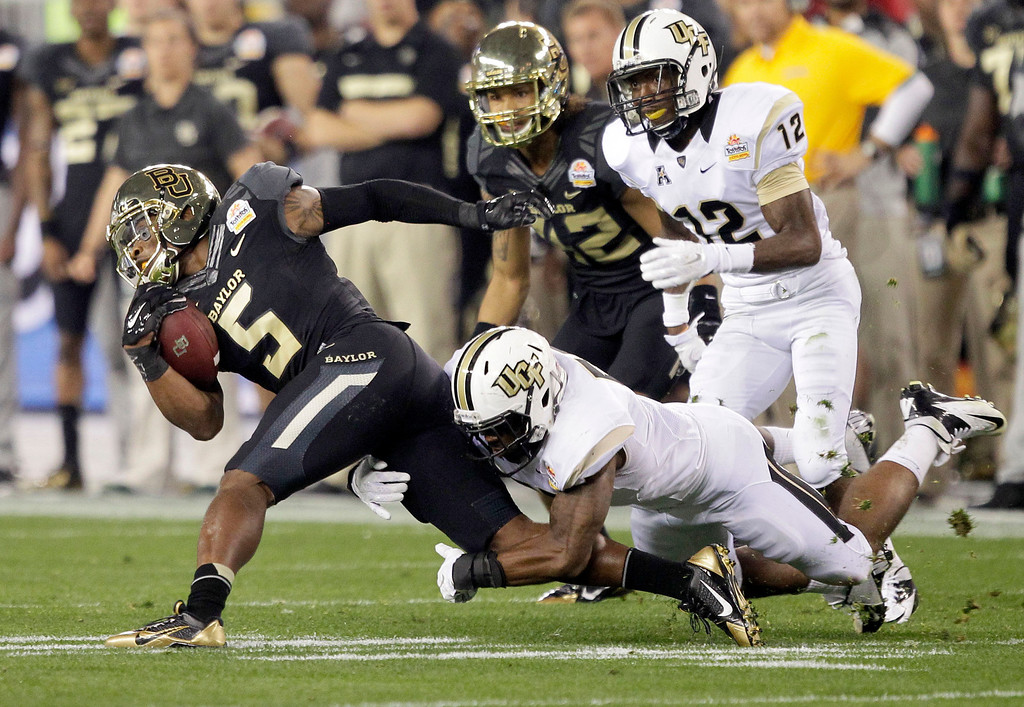 . Baylor wide receiver Antwan Goodley (5) is tackled by Central Florida linebacker Tyler Linde during the first half of the Fiesta Bowl NCAA college football game, Wednesday, Jan. 1, 2014, in Glendale, Ariz. (AP Photo/Rick Scuteri)
