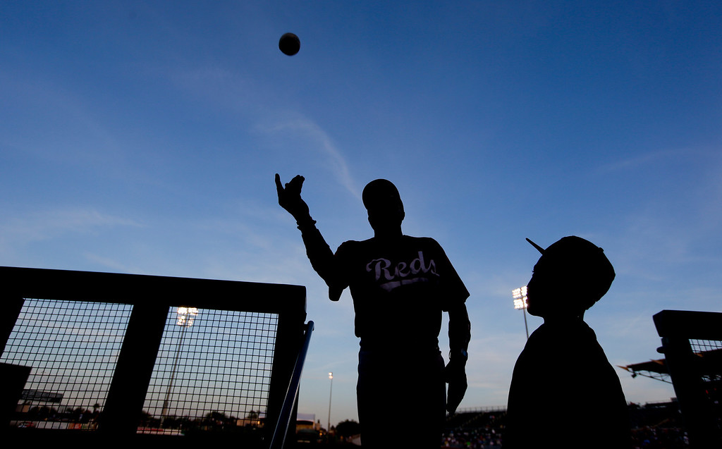 . Cincinnati Reds manager Dusty Baker, left, throws a ball to a fan as his son, Darin, 14, watches before the Reds\' spring training baseball game against the Chicago Cubs in Mesa, Ariz. Tuesday, March 26, 2013. (AP Photo/Chris Carlson)
