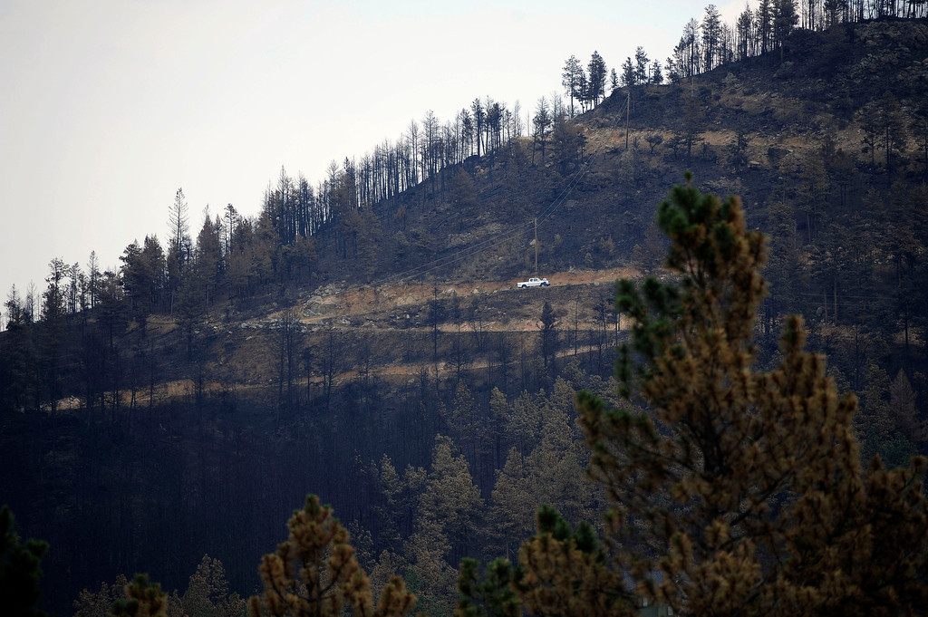 . The hillside across from Pat Baker\'s house in Rist Canyon burned from the High Park Fire. Pat Baker\'s two-story house burned to the ground by the High Park Fire, the fire skipped past several out buildings and missed her neighbors house completely.  Andy Cross, The Denver Post