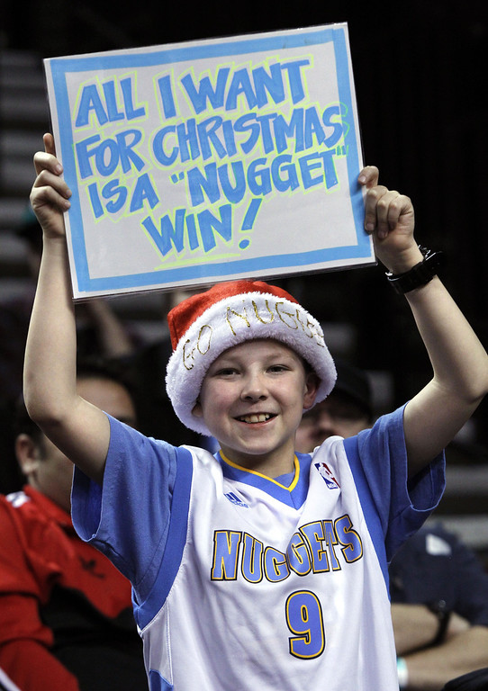 . Denver Nuggets fan Braiden Espinosa holds up a sign during the first quarter of an NBA basketball game with the Portland Trail Blazers in Portland, Ore., Thursday, Dec. 20, 2012. (AP Photo/Don Ryan)