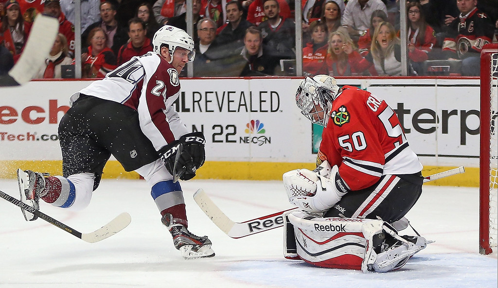 . Corey Crawford #50 of the Chicago Blackhawks makes a save against Marc-Andre Cliche #24 of the Colorado Avalanche at the United Center on January 14, 2014  in Chicago, Illinois. (Photo by Jonathan Daniel/Getty Images)
