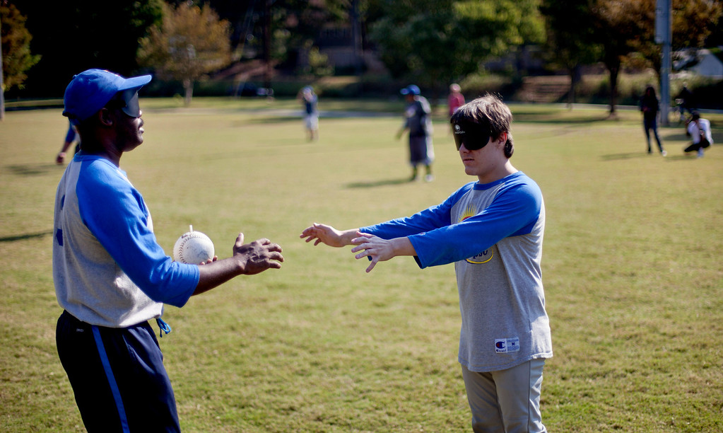 """. Jimmie Burnette, left, who lost his vision to a brain tumor in 2010, reaches out to find teammate Richard Sexton to run through a drill in blind baseball practice in Atlanta on Sept. 22, 2012. \""""Right now, I just try to take it day by day, one step at a time. BEEP baseball is helping me out. It takes away from me thinking about I\'m less than a man,\"""" says Jimmie Burnette. (AP Photo/David Goldman)"""