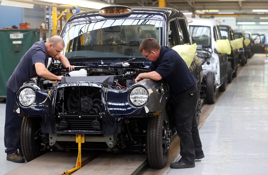 . Steve Wilson (L) and Steve Pearce work on a TX4 London Taxi on the assemby line at the London Taxi Company on September 11, 2013 in Coventry, England. The business secretary, Vince Cable, officially restarted the production line of the iconic TX4 black cabs today, six months after the company behind the famous vehicles was rescued by the Chinese company Geely Group.  (Photo by Matt Cardy/Getty Images)