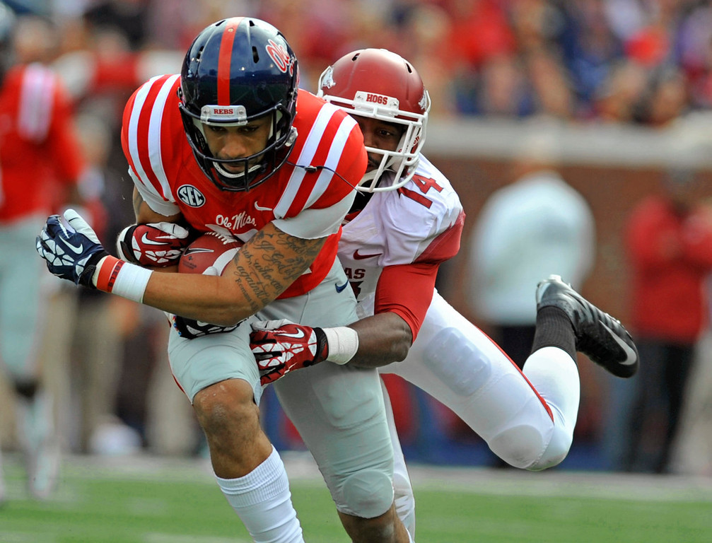 . Arkansas safety Eric Bennett (14) holds onto Mississippi receiver Donte Moncrief (12) during the first half of an NCAA college football game on Saturday, Nov. 9, 2013, in Oxford, Miss. Mississippi won 34-24.  (AP Photo/ The Daily Mississippian, Austin McAfee)