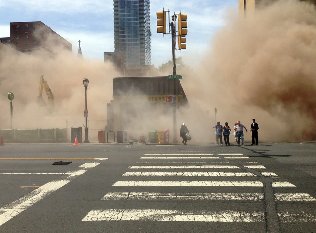 . In this photo provided by Jordan McLaughlin, a dust cloud rises as people run from the scene of a building collapse on the edge of downtown Philadelphia on Wednesday, June 5, 2013. A building that was being torn down collapsed with a thunderous boom, raining bricks on a neighboring thrift store, killing a woman and injuring at least 13 other people in an accident that witnesses said was bound to happen. (AP Photo/Jordan McLaughlin)
