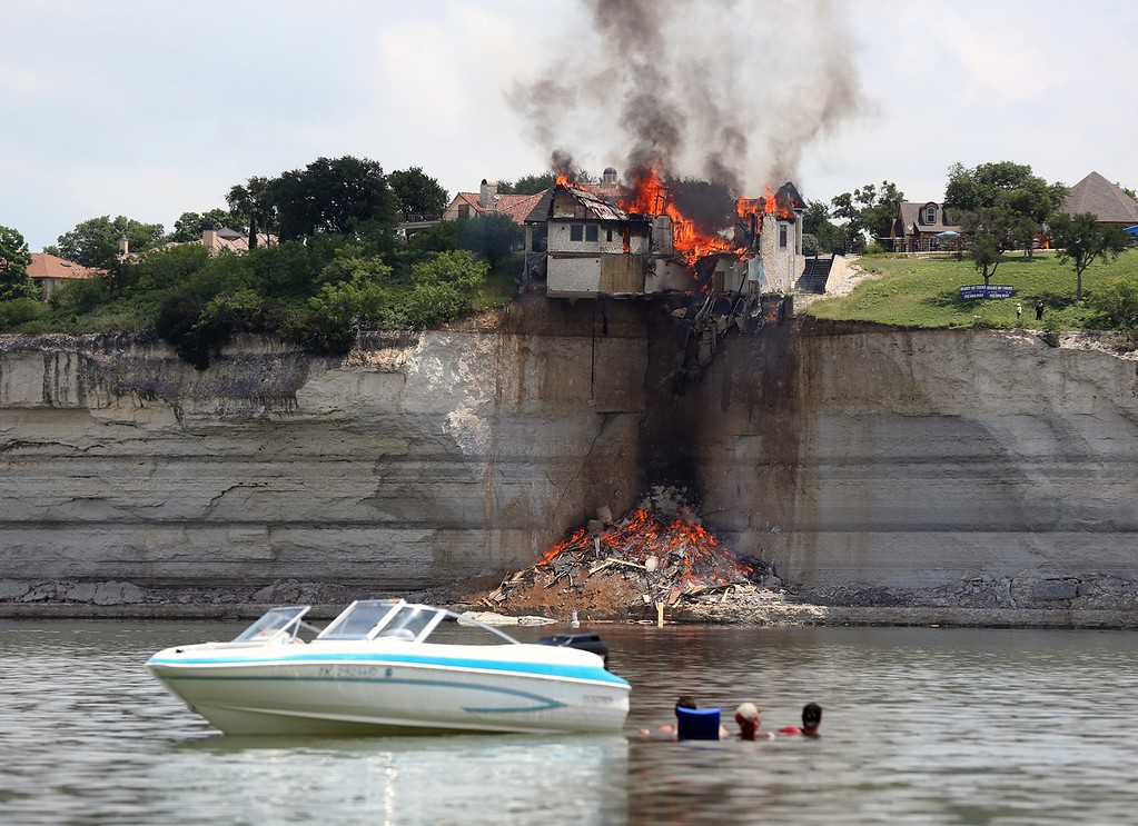 . Boaters watch as a $700,000 vacation home perched on a crumbling cliff overlooking Lake Whitney is engulfed by fire as demolition crews deliberately burned the structure to the ground rather than wait for it to crumble into the water as the land faltered around it, Friday, June 13, 2014, near Whitney, Texas. The house was condemned earlier after a fracture appeared in the bluff on which it was built. (AP Photo/Waco Tribune Herald, Rod Aydelotte)