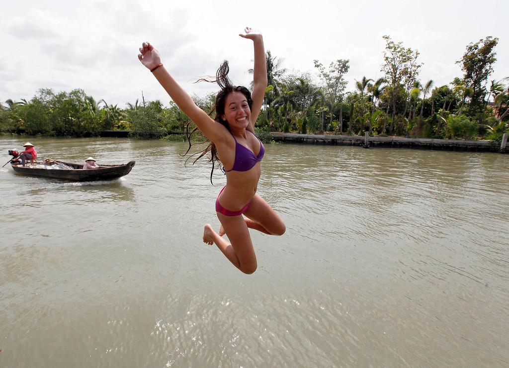 . Sarina Wasserman from Santa Barbara Middle School California jumps into the water at An Binh Island Canal during Spring Break at Vinh Long Province Mekong Delta Vietnam Tuesday, April 2.  2013. (AP Photo/Nick Ut)