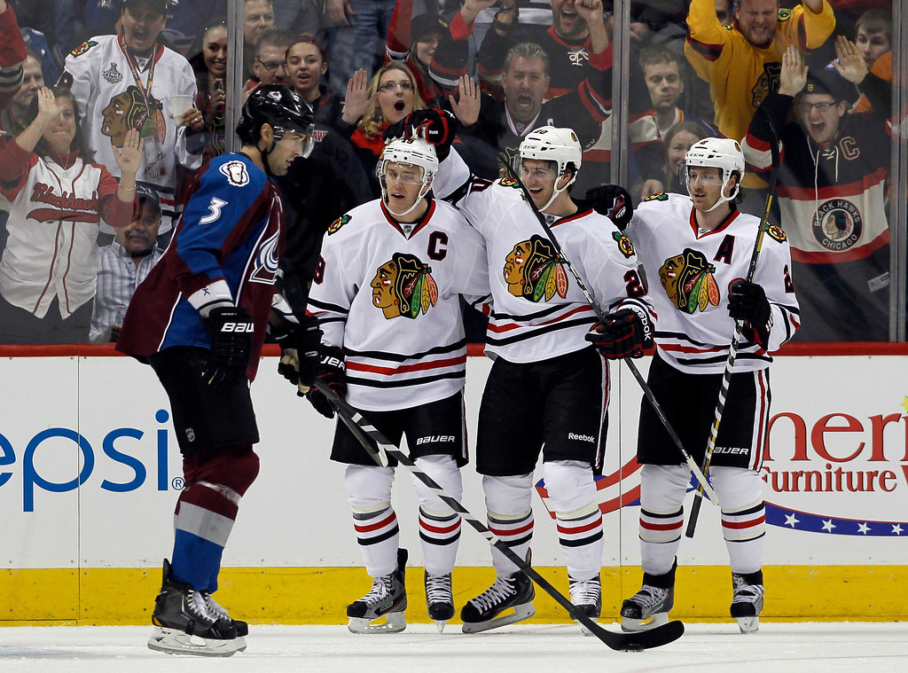 . As Colorado Avalanche defenseman Ryan O\'Byrne, left, looks on, Chicago Blackhawks center Jonathan Toews, second from left, is congratulated after scoring a goal by teammates Brandon Saad, third from left, and Duncan Keith in the first period of an NHL hockey game in Denver, Friday, March 8, 2013. (AP Photo/David Zalubowski)