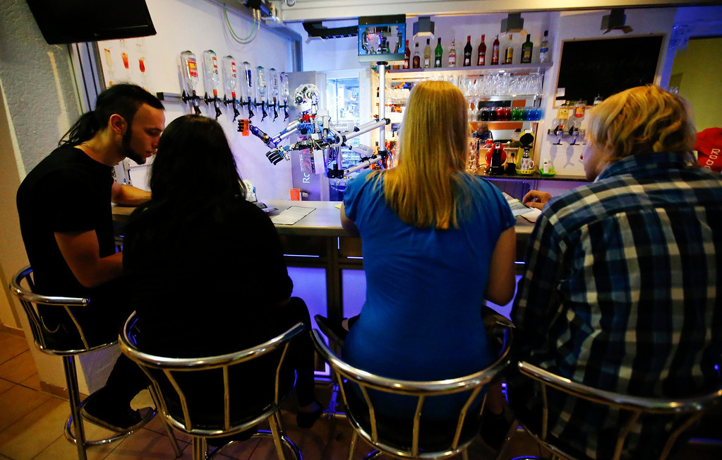 """. Humanoid robot bartender \""""Carl\"""" fills a cocktail glass with spirits to prepare a drink for a guest at the Robots Bar and Lounge in the eastern German town of Ilmenau, July 26, 2013.\""""Carl\"""", developed and built by mechatronics engineer Ben Schaefer who runs a company for humanoid robots, prepares spirits for the mixing of cocktails and is able to interact with customers in small conversations. Picture taken July 26, 2013. REUTERS/Fabrizio Bensch"""