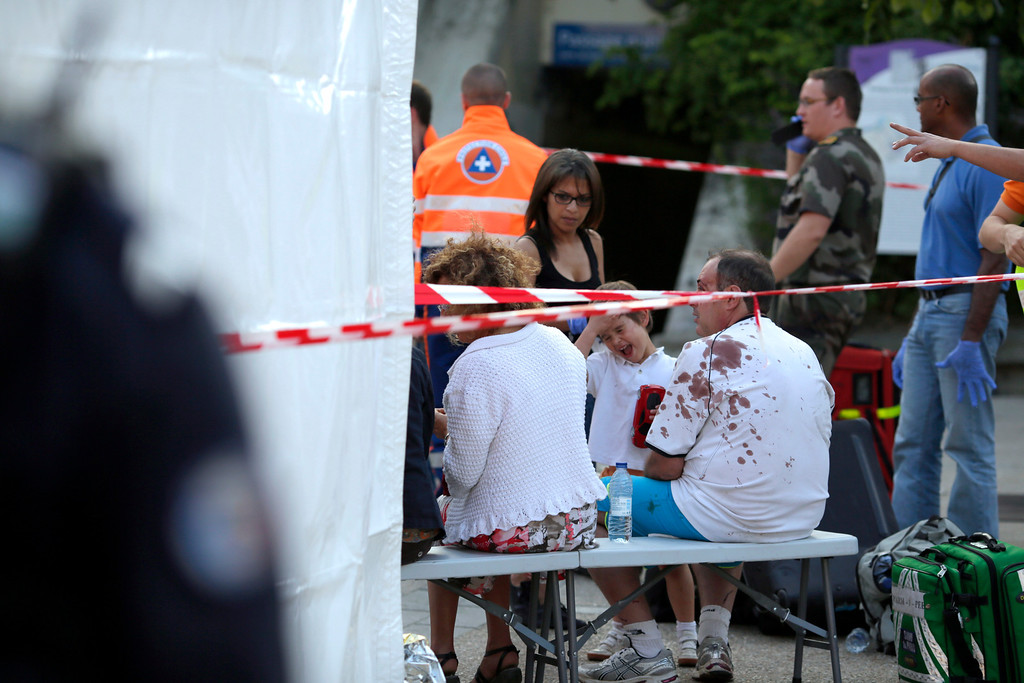 . A man with a blood-splattered shirt sits on a bench among victims and emergency workers,  on the site of a train accident in the railway station of Bretigny-sur-Orge, Friday, July 12, 2013 near Paris.  (AP Photo/Kenzo Tribouillard, Pool)