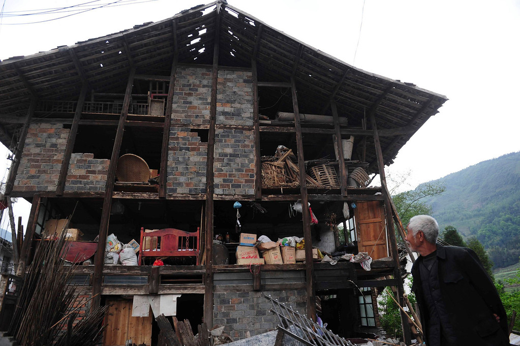 . A man looks at a damaged house at Taiping township, Lushan county, Sichuan province, April 24, 2013. The earthquake so far left 196 dead, 21 missing and 11,470 injured, according to Xinhua News Agency. Picture taken April 24.    REUTERS/China Daily
