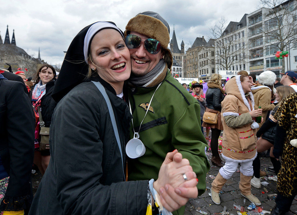 ". A woman dressed as a nun and a man as a pilot dance in the street when tens of thousands revelers dressed in carnival costumes celebrate the start of the street-carnival on the so called ""Old Women\'s Day\"" in the party capital Cologne, Germany, Thursday, Feb. 27, 2014. (AP Photo/Martin Meissner)"