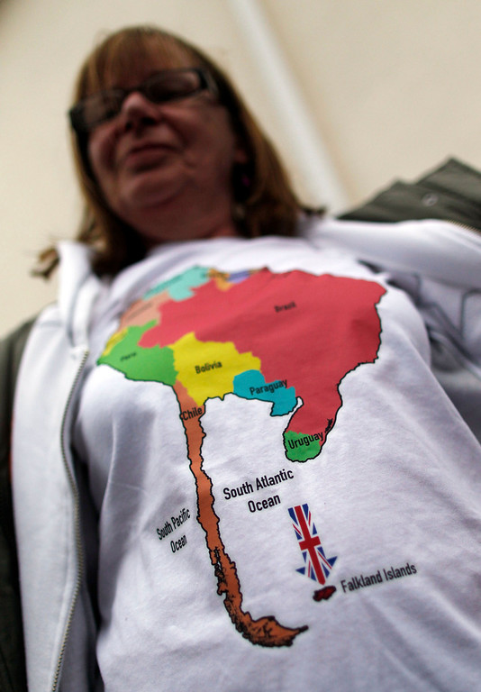 . Falkland Islander Vivian Vienna shows off her t-shirt as she lines up to cast her vote at the Town Hall polling station in Stanley March 10, 2013. Voters in the remote British-ruled Falkland Islands hold a referendum on their future today that seeks to challenge Argentina\'s increasingly vocal sovereignty claim. The drawing on the t-shirt is a map of South America that does not include Argentina. REUTERS/Marcos Brindicci
