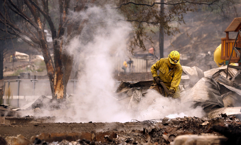 . A firefighter works on the still-smoldering home of the mayor of Pateros, Wash., Friday, July 18, 2014. A fire racing through rural north-central Washington destroyed about 100 homes, leaving behind smoldering rubble, solitary brick chimneys and burned-out automobiles as it blackened hundreds of square miles. Friday\'s dawn revealed dramatic devastation, with the Okanagan County town of Pateros, home to 650 people, hit especially hard. (AP Photo/Elaine Thompson)