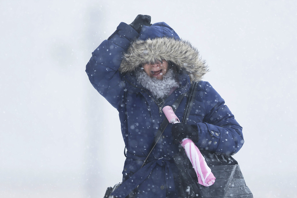 . A woman holds onto her hood as the wind blows during a winter snowstorm Tuesday, Jan. 21, 2014, in Philadelphia. A storm is sweeping across the Mid-Atlantic and New England.   (AP Photo/Matt Rourke)