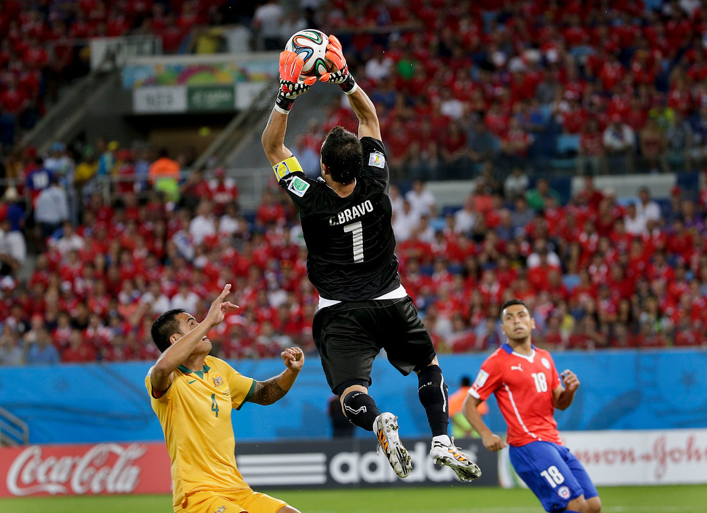 . Chile\'s goalkeeper Claudio Bravo leaps above Australia\'s Tim Cahill to claim the ball during the group B World Cup soccer match between Chile and Australia at the Arena Pantanal in Cuiaba, Brazil, Friday, June 13, 2014. (AP Photo/Felipe Dana)