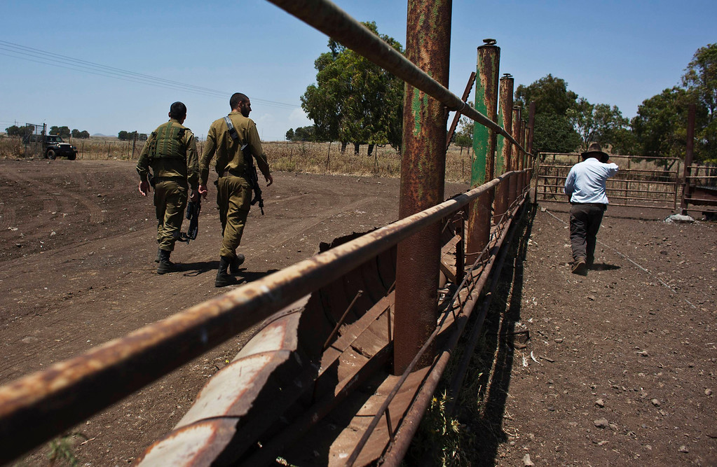 . Nadav (R), the chief cowboy of the Yonatan herd, walks next to Israeli soldiers on a ranch just outside Moshav Yonatan, a collective farming community, about 2 km (1 mile) south of the ceasefire line between Israel and Syria in the Golan Heights May 21, 2013. REUTERS/Nir Elias