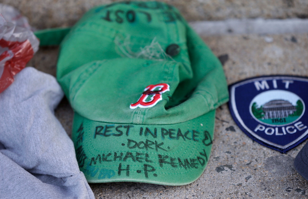 . A baseball cap with a written tribute to fallen Boston firefighter Michael Kennedy rests at a makeshift memorial in front of fire station Engine 33, Thursday, March 27, 2014, in Boston. Fire station Engine 33 was the station of fallen firefighters Kennedy and Lt. Edward Walsh and who lost their lives fighting a 9-alarm fire in a four-story brownstone in Boston\'s Back Bay neighborhood Wednesday, March 26, 2014. (AP Photo/Steven Senne)