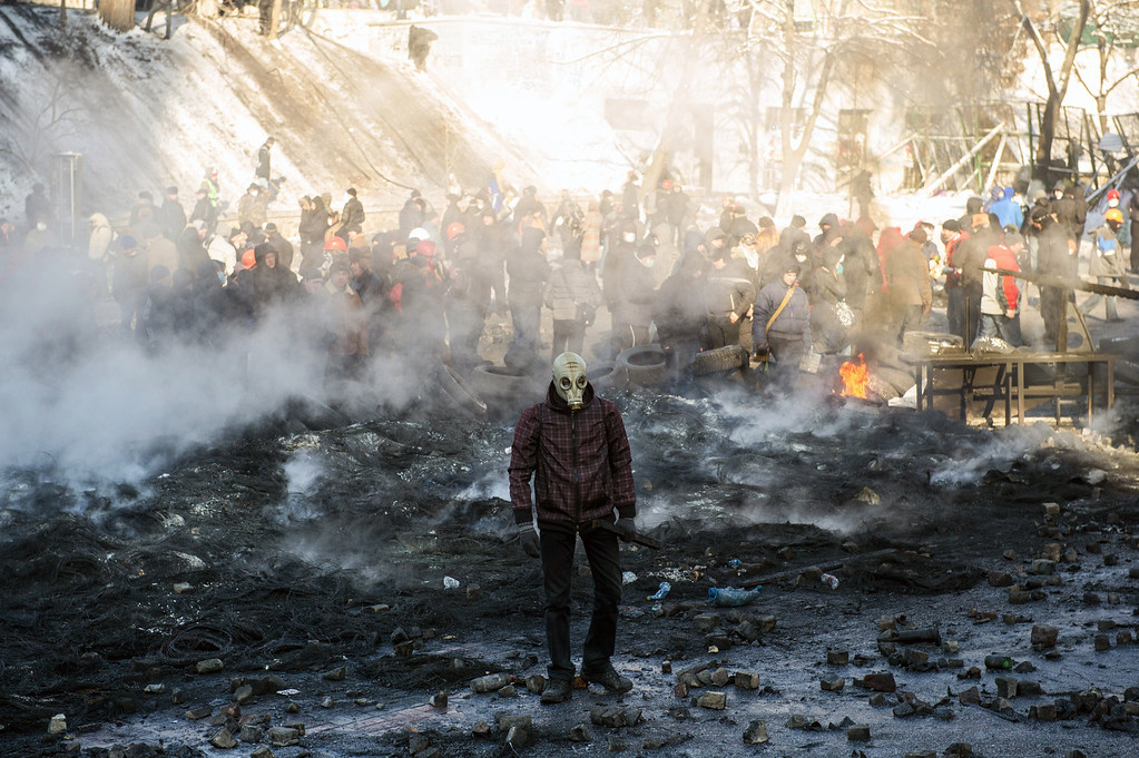 . A protester wearing a gas mask stands amid burnt tyres and garbage following clashes between pro-EU demonstrators and riot police in Kiev on January 23, 2014. Ukraine\'s opposition agreed to observe an eight-hour truce in clashes with security forces after five days of deadly fighting but threatened to go on the attack if the government failed to agree concessions. Opposition leader and world boxing champion Vitali Klitschko brokered the truce after talks with radical protesters and armored security forces on the frontline of the clashes, saying the ceasefire should hold while he conducts talks with President Viktor Yanukovych. AFP PHOTO/VOLODYMYR  SHUVAYEV/AFP/Getty Images