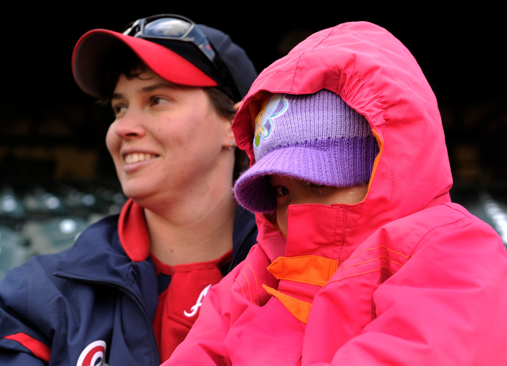 . DENVER, CO. - APRIL 23:  Claire Howard, left, and Reese Rohrs, age 3, shivered through the game at Coors Field Tuesday afternoon. The Atlanta Braves defeated the Colorado Rockies 4-3 at Coors Field Tuesday, April 23, 2013.  The first game of the doubleheader Tuesday was a make-up from Monday night\'s postponement due to weather.  Photo By Karl Gehring/The Denver Post