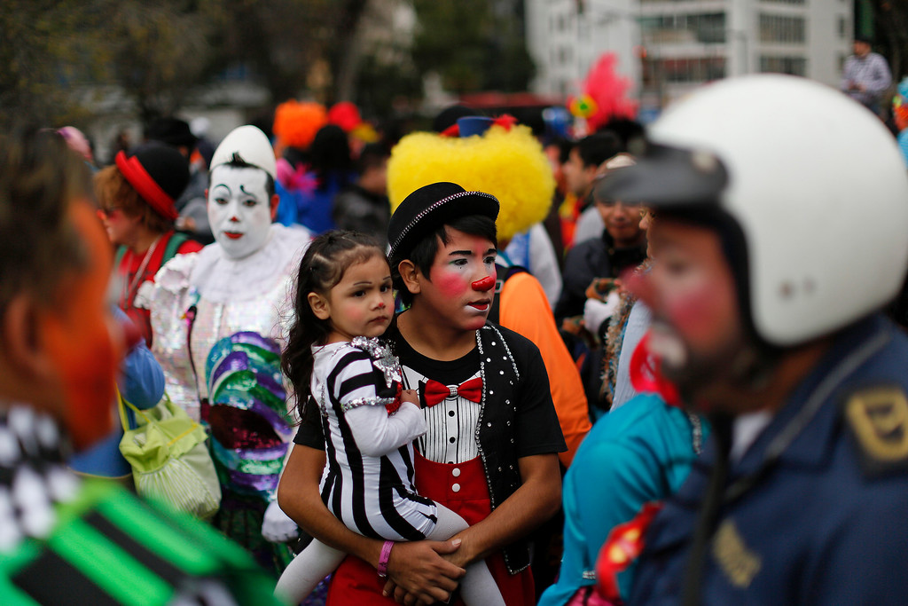 . A clown carrying his daughter waits for the start of a laugh-a-thon at the 17th International Clown Convention in Mexico City, Wednesday, Oct. 23, 2013. They sought a world laugh record but no Guinness official was seen present and they fell short of 15 minutes. (AP Photo/Dario Lopez-Mills)
